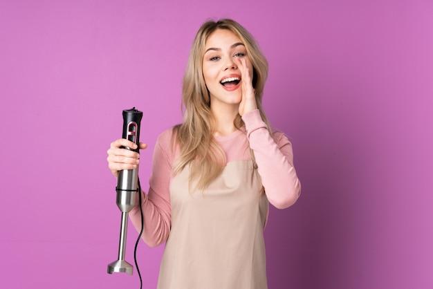 Adolescente ragazza russa utilizzando frullatore a immersione isolato su viola gridando con la bocca spalancata