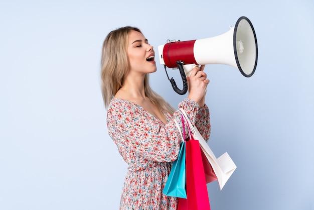 Ragazza russa dell'adolescente con il sacchetto della spesa sulla parete blu che grida tramite un megafono