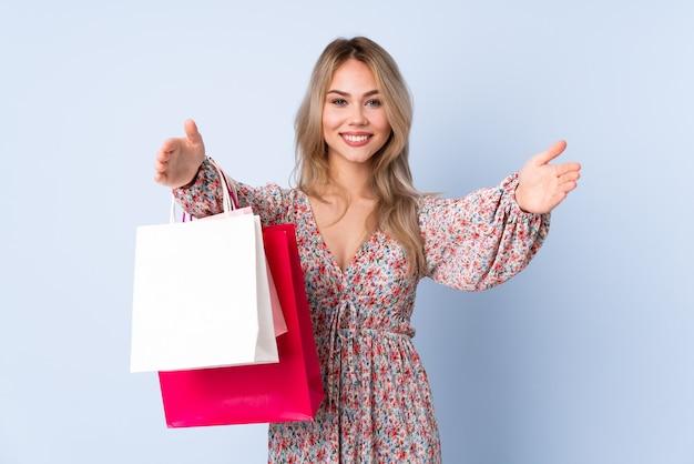 Ragazza russa dell'adolescente con il sacchetto della spesa isolato sulla parete blu che presenta e che invita a venire con la mano