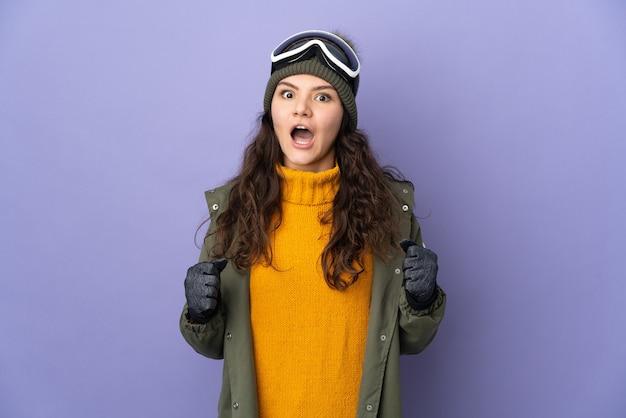 Ragazza russa dell'adolescente con occhiali da snowboard isolati sulla parete viola che celebra una vittoria nella posizione del vincitore