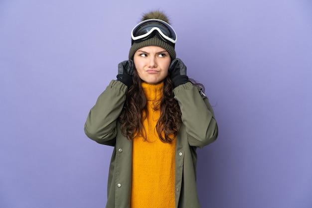 Ragazza russa dell'adolescente con gli occhiali di snowboard isolati sulla parete viola frustrata e che copre le orecchie