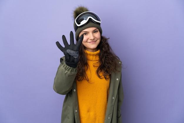 Ragazza russa dell'adolescente con gli occhiali da snowboard isolati sulla parete viola felice e contando quattro con le dita