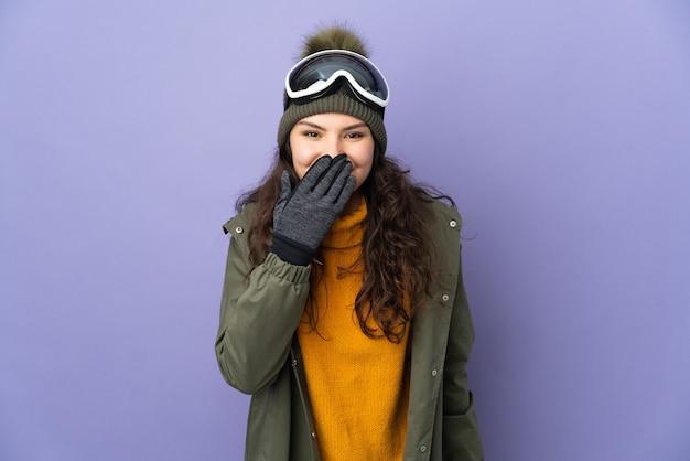 Adolescente ragazza russa con occhiali da snowboard isolati sulla parete viola felice e sorridente che copre la bocca con la mano