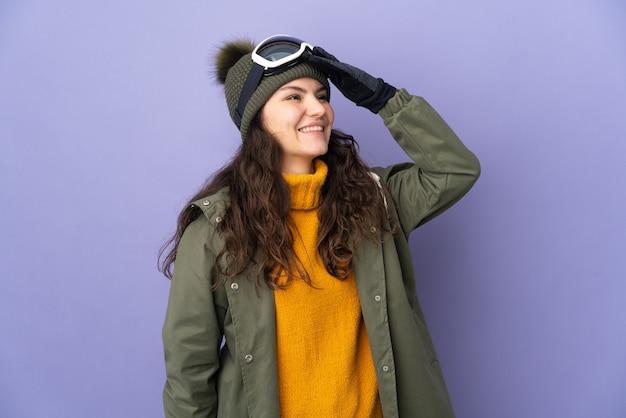 Ragazza russa dell'adolescente con gli occhiali di snowboard isolati sulla parete viola che sorride molto