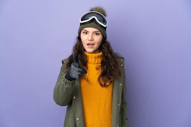 Ragazza russa dell'adolescente con gli occhiali di snowboard isolati sulla parete viola sorpresa e che indica la parte anteriore