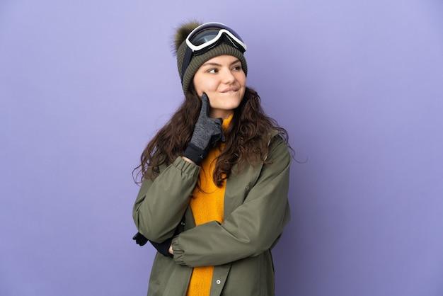 Ragazza russa dell'adolescente con gli occhiali di snowboard isolati sulla parete viola che pensa un'idea mentre osserva in su