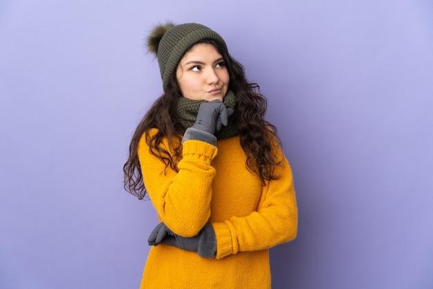 Adolescente ragazza russa con cappello invernale isolato su sfondo viola e guardando in alto
