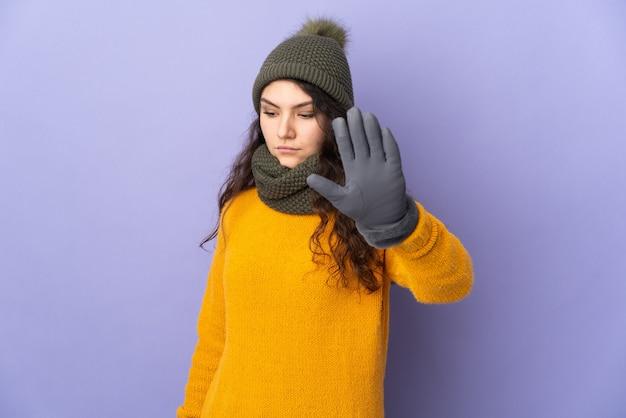 Adolescente ragazza russa con cappello invernale isolato su sfondo viola che fa gesto di arresto e deluso