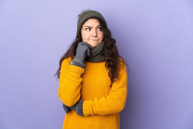 Adolescente ragazza russa con cappello invernale isolato su superficie viola con dubbi e pensieri