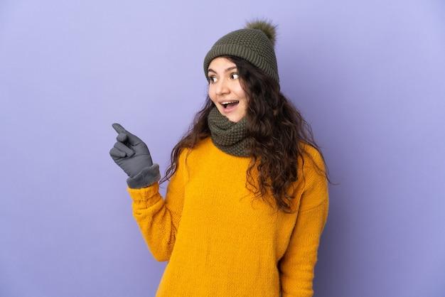 Adolescente ragazza russa con cappello invernale isolato su superficie viola con l'intenzione di realizzare la soluzione sollevando un dito