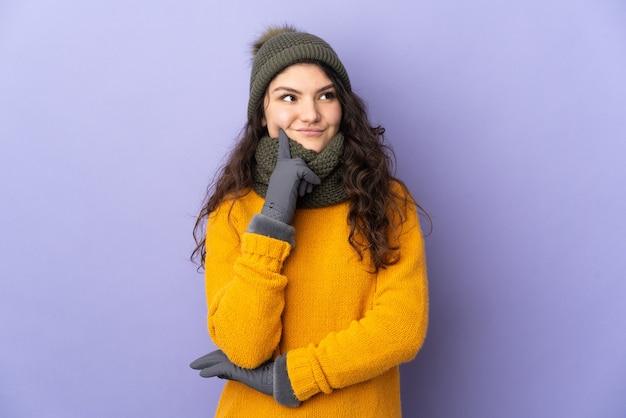 Ragazza russa dell'adolescente con il cappello di inverno isolato sulla parete viola che pensa un'idea mentre osserva in su