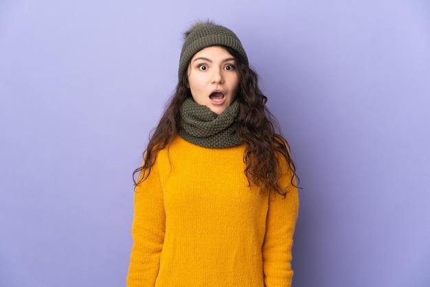 Ragazza russa dell'adolescente con il cappello di inverno isolato sulla parete viola con l'espressione facciale di sorpresa