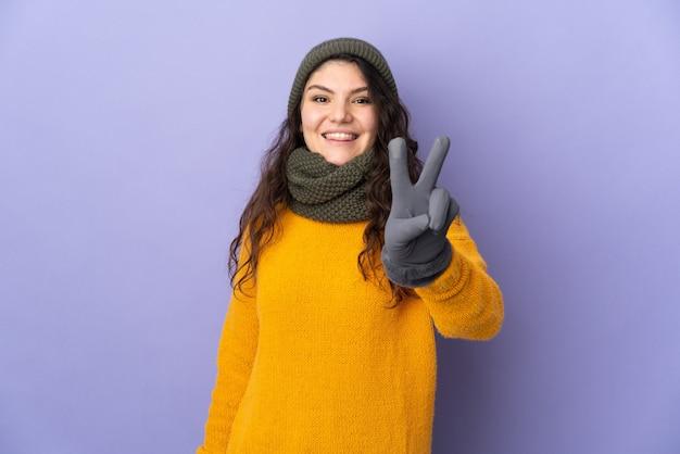 Ragazza russa dell'adolescente con il cappello di inverno isolato
