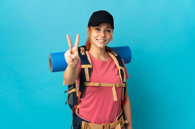 Ragazza russa dell'escursionista dell'adolescente isolata sulla parete blu che sorride e che mostra il segno di vittoria
