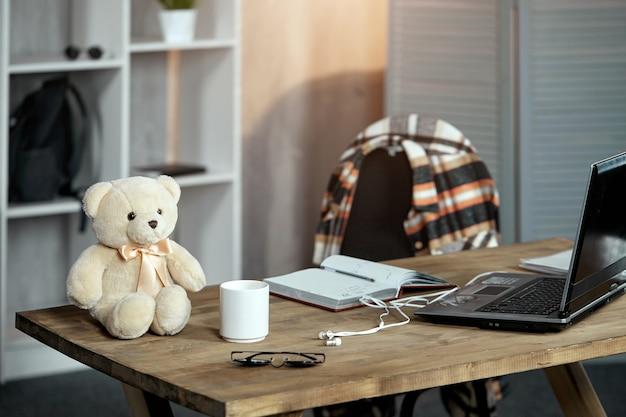 Il posto di lavoro di un adolescente, una scrivania con un laptop e un orsacchiotto