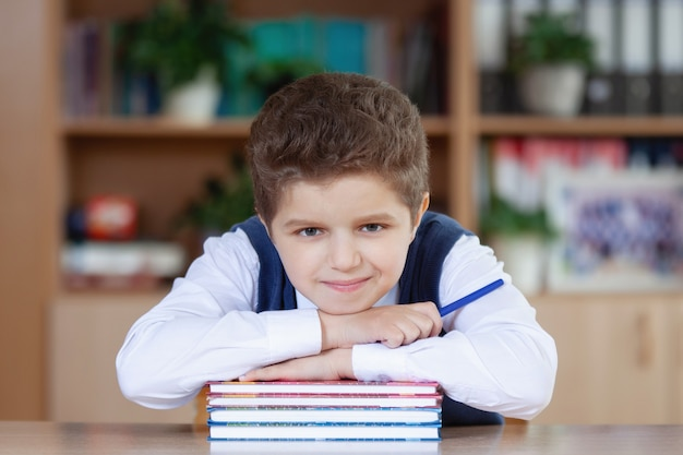 Scolaro adolescente seduto a un tavolo con una pila di libri, sorridente e guardando la telecamera.