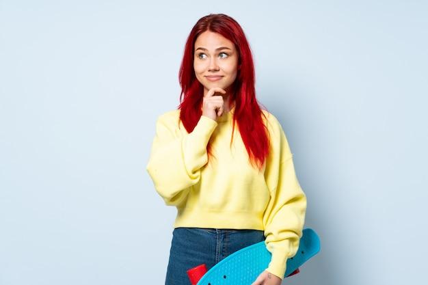 Donna del pattinatore dell'adolescente isolata sulla parete bianca che ha dubbi e pensare