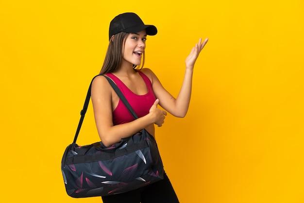 Ragazza sportiva adolescente con borsa sportiva che estende le mani di lato per invitare a venire