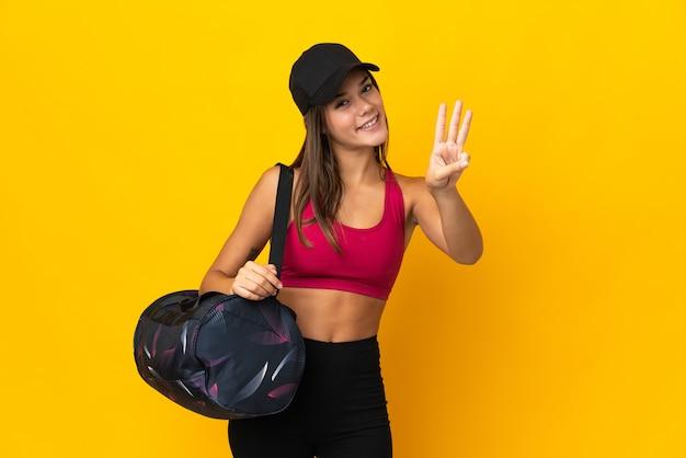Ragazza di sport dell'adolescente con la borsa di sport felice e che conta tre con le dita