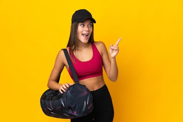 Ragazza sportiva adolescente con borsa sportiva che intende realizzare la soluzione alzando un dito