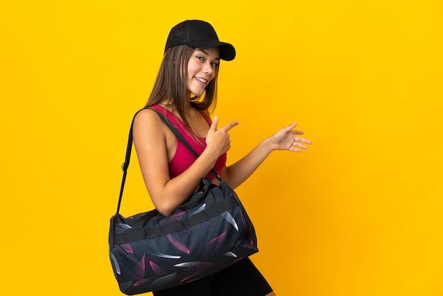 Ragazza di sport dell'adolescente con la borsa di sport che indica il dito a lato