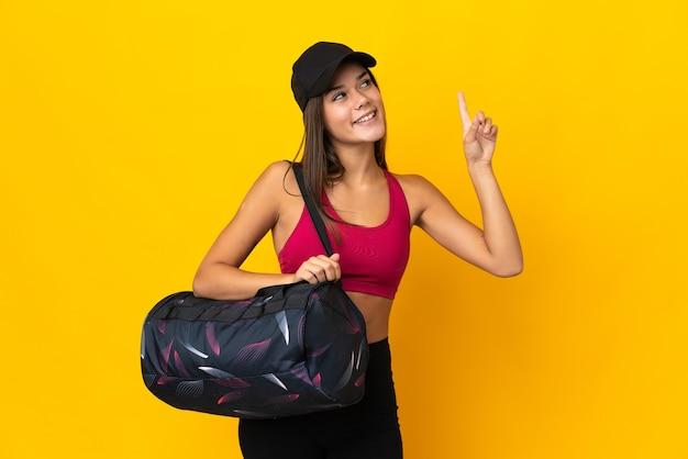 Ragazza di sport dell'adolescente con la borsa di sport che indica su una grande idea