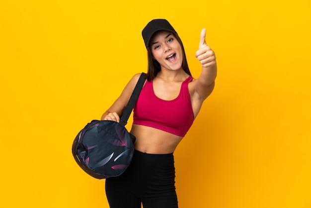 Ragazza sportiva adolescente con borsa sportiva con i pollici in su perché è successo qualcosa di buono