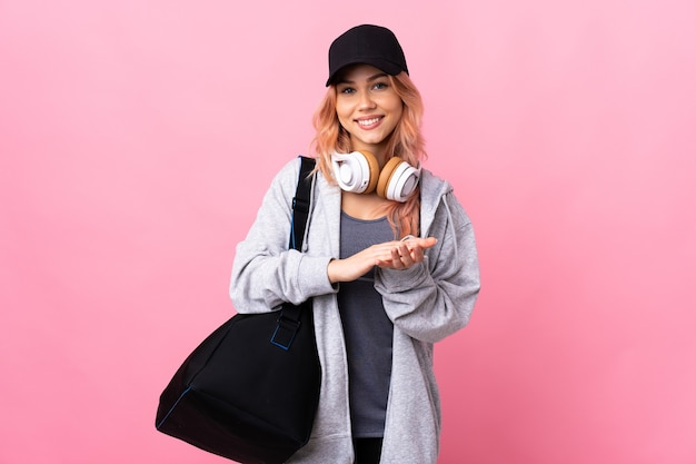 Adolescente donna sportiva con borsa sportiva su sfondo isolato che applaude