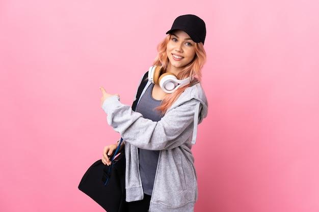 Donna di sport dell'adolescente con la borsa di sport sopra la parete isolata che indica indietro