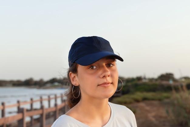 Adolescente in piedi in riva al mare al tramonto e guardando dritto in telecamera. ragazza teenager che indossa t-shirt e berretto da baseball blu scuro. colpo di testa. modello di berretto