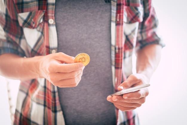 Adolescente in piedi e giocando con bitcoin e guardando il suo telefono