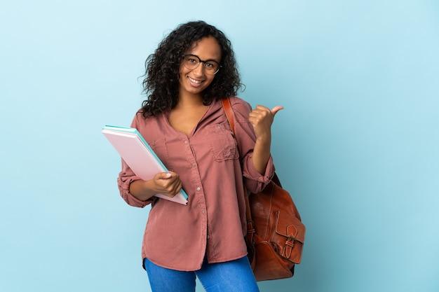 Ragazza dell'allievo dell'adolescente isolata sulla parete blu che indica al lato per presentare un prodotto