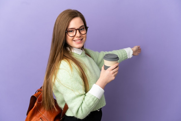 Ragazza studentessa adolescente su sfondo viola isolato che estende le mani di lato per invitare a venire