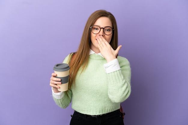 Ragazza studentessa adolescente su sfondo viola isolato felice e sorridente che copre la bocca con la mano