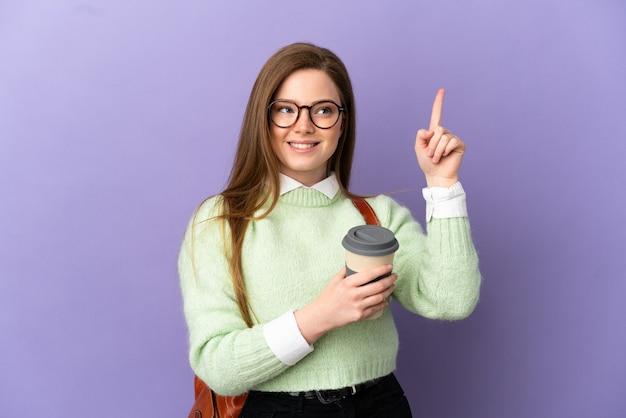 Ragazza studentessa adolescente su sfondo viola isolato che punta verso l'alto una grande idea