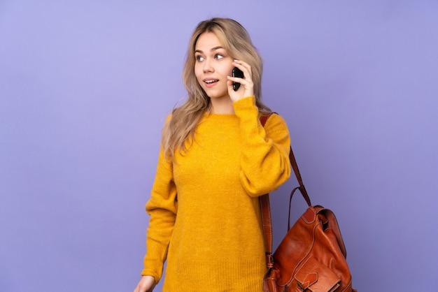 Ragazza dello studente dell'adolescente isolata sulla parete viola che mantiene una conversazione con il telefono cellulare con qualcuno
