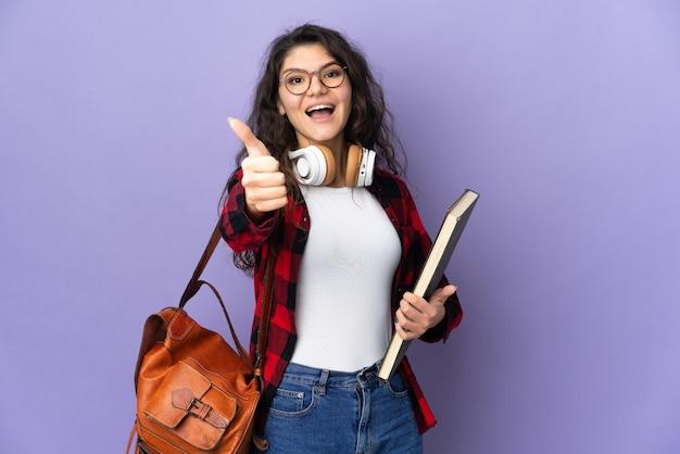 Studente adolescente isolato su sfondo viola con i pollici in su perché è successo qualcosa di buono