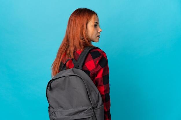 Ragazza russa dell'allievo dell'adolescente sull'azzurro nella posizione posteriore e guardando indietro