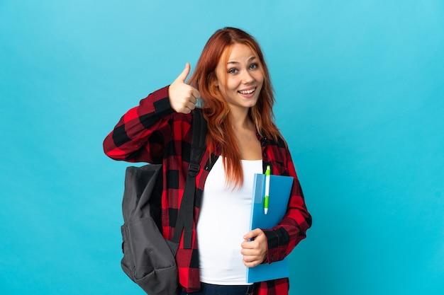 Ragazza russa dell'allievo dell'adolescente sull'azzurro che dà i pollici aumenta il gesto