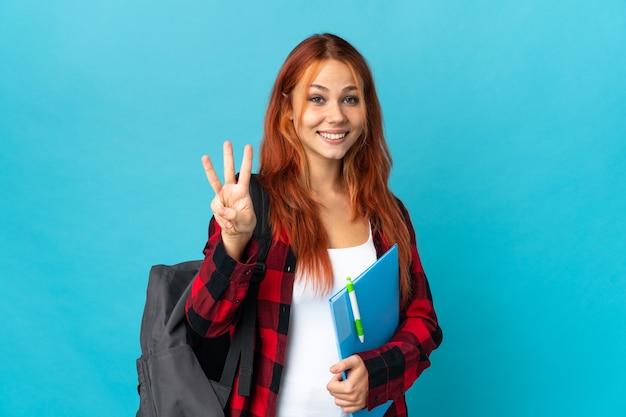 Ragazza russa dell'allievo dell'adolescente sull'azzurro felice e che conta tre con le dita
