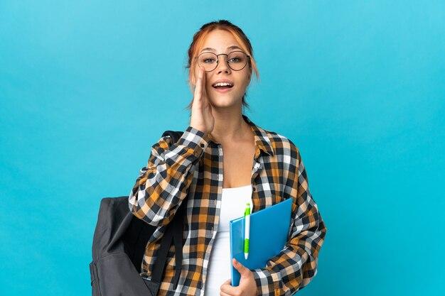Ragazza russa dell'allievo dell'adolescente sull'azzurro che grida con la bocca spalancata