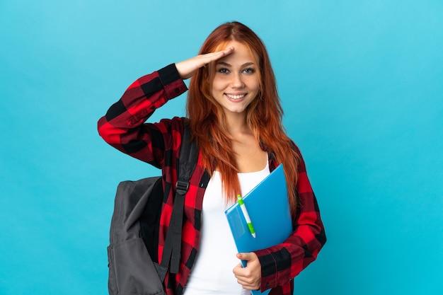 Ragazza russa dell'allievo dell'adolescente isolata sull'azzurro che saluta con la mano con l'espressione felice