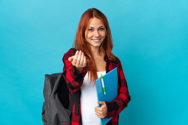 Ragazza russa dell'allievo dell'adolescente isolata sulla parete blu che invita a venire con la mano.