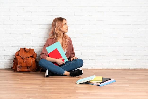 Donna dell'allievo dell'adolescente con i capelli rosa che si siede sul pavimento al chiuso in posizione laterale