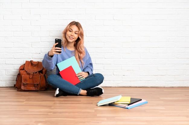 Donna dell'allievo dell'adolescente con i capelli rosa che si siede sul pavimento in interni facendo un selfie
