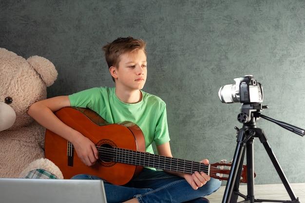 L'adolescente toglie il vlog di un gioco su una chitarra a casa sulla fotocamera. il giovane ragazzo adolescente videobloger sta imparando a suonare la chitarra online in salotto,