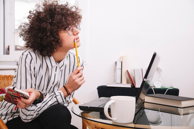 Adolescente che pensa vicino al computer portatile