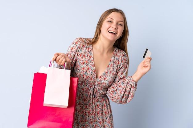 Ragazza ucraina dell'adolescente che tiene i sacchetti della spesa e una carta di credito