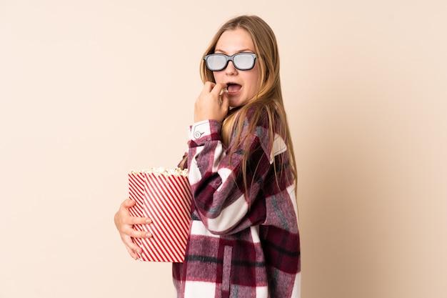 Ragazza ucraina dell'adolescente isolata su beige con i vetri 3d e tenere un grande secchio di popcorn mentre osservando lato
