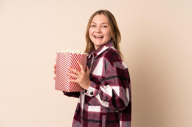 Donna ucraina dell'adolescente isolata su spazio beige che tiene un grande secchio di popcorn